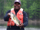 An Army veteran shows off the largemouth bass he caught during the Fishing with Veterans event at Rough River Lake, Falls of Rough, Ky., May 11, 2013. (U.S. Army Corps of Engineers photo by Diane Stratton)